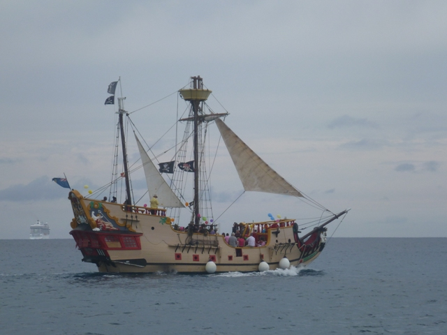 the local pirate ship passing while a cruise ships leaves